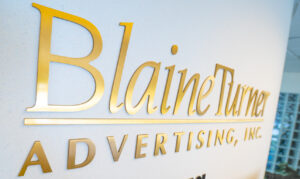 BlaineTurner Advertising's text logo, written in gold font, is mounted on the agency's wall.